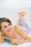 Mulher feliz que coloca na cama com bloco dos comprimidos Imagem de Stock