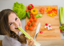 Mulher feliz que come o aipo na cozinha Foto de Stock Royalty Free