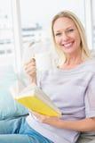 Mulher feliz que come o café quando livro de leitura no sofá foto de stock