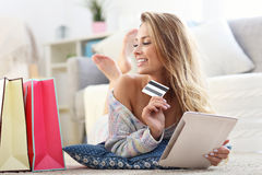 Mulher feliz que compra em linha com cartão de crédito fotografia de stock royalty free