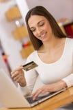 Mulher feliz que compra em linha com cartão e computador de crédito. Interno Fotografia de Stock Royalty Free