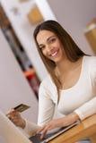 Mulher feliz que compra em linha com cartão e computador de crédito. Interno Imagens de Stock Royalty Free