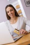 Mulher feliz que compra em linha com cartão e computador de crédito. Interno Fotografia de Stock