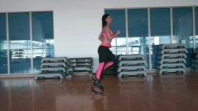 Mulher feliz que corre com as sapatas do kangoo no gym video estoque