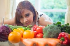 Mulher feliz que cozinha a salada verde dos vegetais Fotos de Stock Royalty Free