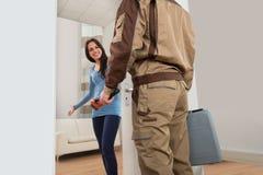 Mulher feliz que dá boas-vindas ao encanador em casa Fotografia de Stock Royalty Free