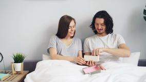 Mulher feliz que dá a homem o teste de gravidez positivo na caixa de presente na cama em casa filme