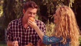 Mulher feliz que dá a maçã a seu marido vídeos de arquivo