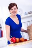 Mulher feliz que desembala mantimentos na cozinha Imagens de Stock Royalty Free