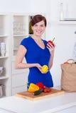 Mulher feliz que desembala mantimentos na cozinha Foto de Stock Royalty Free