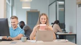 Mulher feliz que encontra o presente no local de trabalho Consideravelmente ruído de escuta da senhora dentro da caixa vídeos de arquivo