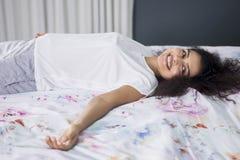 Mulher feliz que encontra-se na cama imagem de stock royalty free