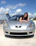 Mulher feliz que encontra-se na capa do carro imagens de stock