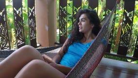 Mulher feliz que encontra-se na rede que relaxa na câmera pov da ação do terraço do verão da moça que tem o resto filme
