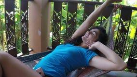 Mulher feliz que encontra-se na rede que relaxa na câmera pov da ação do terraço do verão da moça que tem o resto vídeos de arquivo