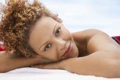 Mulher feliz que encontra-se na tabela da massagem imagens de stock