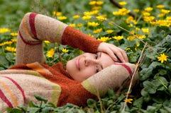 Mulher feliz que encontra-se no campo das flores imagem de stock