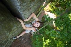 Mulher feliz que escala em uma corda rochosa da parede, bouldering foto de stock