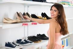 Mulher feliz que escolhe sapatas da prateleira na loja Fotos de Stock