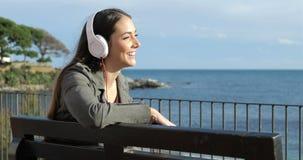 Mulher feliz que escuta a música que senta-se em um banco filme