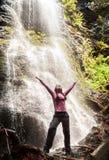 Mulher feliz que está na frente da cachoeira fotos de stock