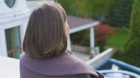 A mulher feliz que está no balcão da propriedade, ar fresco de respiração, fixou a vida vídeos de arquivo