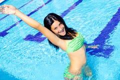 Mulher feliz que está no sorriso da piscina bonito fotografia de stock