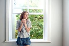 Mulher feliz que está pela janela que sorri com xícara de café Imagem de Stock