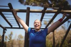 Mulher feliz que exercita durante o curso de obstáculo fotos de stock