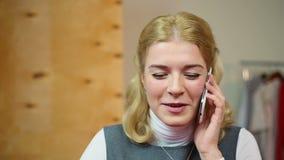 Mulher feliz que fala com um amigo no telefone celular, tendo o divertimento e o sorriso video estoque