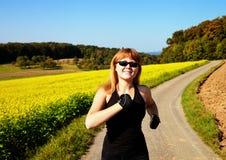 Mulher feliz que funciona em um campo Imagens de Stock