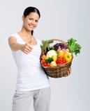 Mulher feliz que guarda a cesta de vegetais crus Imagem de Stock Royalty Free