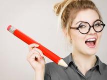 Mulher feliz que guarda o lápis desproporcionado grande imagens de stock