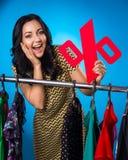 Mulher feliz que guarda o sinal de por cento na cremalheira da roupa com vestido Imagens de Stock Royalty Free