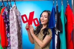 Mulher feliz que guarda o sinal de por cento na cremalheira da roupa com vestido Imagem de Stock Royalty Free