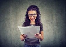 Mulher feliz que guarda papéis com resultados fotografia de stock