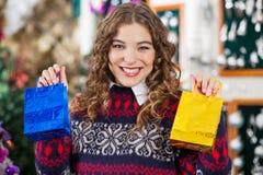 Mulher feliz que guarda sacos de compras pequenos na loja Foto de Stock Royalty Free