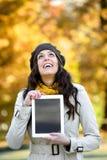 Mulher feliz que guarda a tabuleta digital no outono fotografia de stock royalty free
