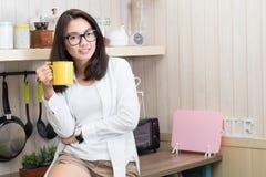 Mulher feliz que guarda um copo na sala da cozinha fotos de stock royalty free