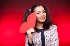 Mulher feliz que guarda um coração do papper nas mãos Fotografia de Stock