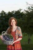 Mulher feliz que guarda uma cesta com ameixas Imagens de Stock