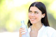 Mulher feliz que guarda uma garrafa da água que olha o lado fotos de stock