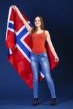 Mulher feliz que guarda uma grande bandeira de Noruega Imagem de Stock Royalty Free