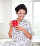 Mulher feliz que guarda uma xícara de café em sua cozinha Imagem de Stock