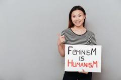 Mulher feliz que guarda vazia com texto sobre o feminismo fotografia de stock