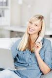 Mulher feliz que guardara um cartão e um portátil de crédito Imagem de Stock