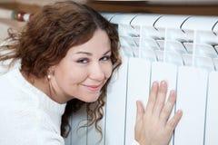 Mulher feliz que inclina o seu ao radiador de aquecimento Imagens de Stock