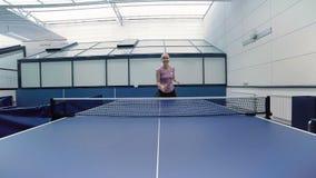 Mulher feliz que joga o tênis de mesa na corte vídeos de arquivo