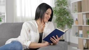 Mulher feliz que lê um livro que senta-se em casa video estoque