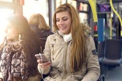 Mulher feliz que lê uma mensagem em seu telefone celular imagens de stock